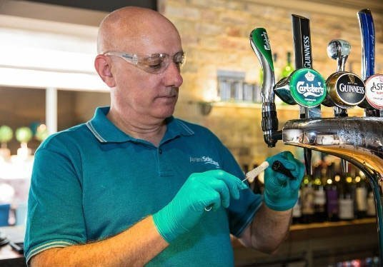 man cleaning beer taps