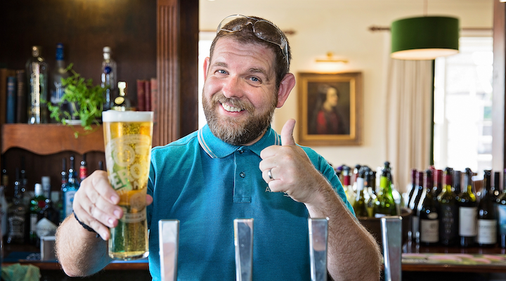 beer ready man in pub giving thumbs up with a pint